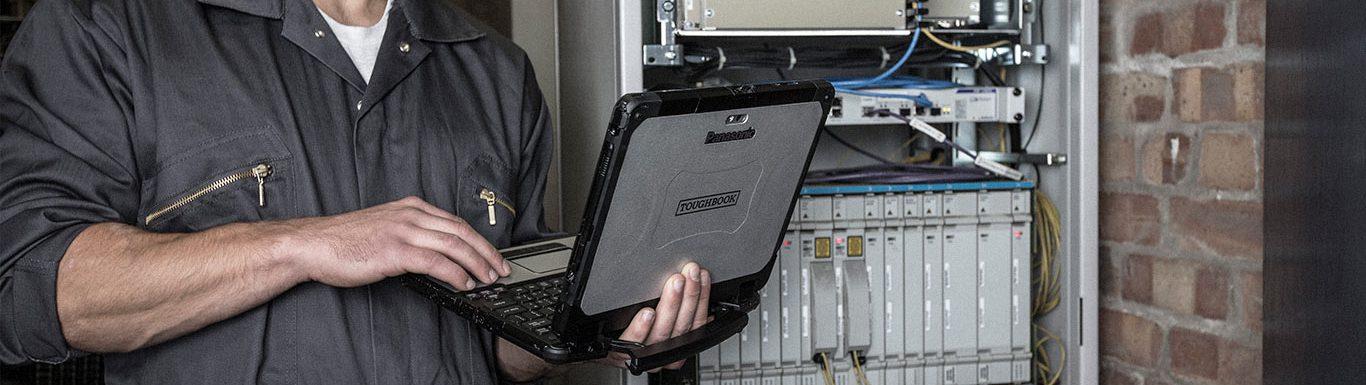 Opérateur de maintenance effectuant un test de connectivité à l'aide d'un ordinateur professionnel