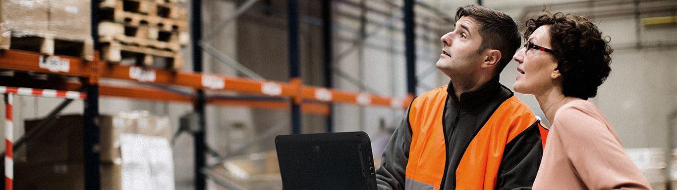 Spécialiste des résaux sans fil effectuant un contrôle en entrepôt avec son client